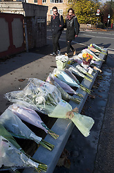 © Licensed to London News Pictures. 13/11/2016. Croydon, UK. A couple look at floral tributes placed on a bridge overlooking the tramline. Engineers work to restore the line at the site where seven people died and 50 were injured when a tram rolled over on Wednesday 9th November. Photo credit: Peter Macdiarmid/LNP