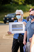 """08 AUGUST 2020 - WEST DES MOINES, IOWA: A person with a Blue Lives Matter placard stands in the parking lot of the West Des Moines Law Enforcement Center before a pro-police rally. About 100 people gathered at the West Des Moines Law Enforcement Center to rally in support of law enforcement. The rally was organized by """"Uplifting Our Police,"""" a local organization that supports law enforcement. They rallied at Des Moines Police headquarters in July. They are planning similar rallies at police stations in the Des Moines metropolitan area.      PHOTO BY JACK KURTZ"""