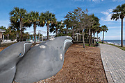 A whale sculpture in Neptune park with the St. Simons Lighthouse behind along the Saint Simons Sound in St. Simons Island, Georgia. The working lighthouse was built in first constructed in 1807 but destroyed by Confederate forces in 1862 before being rebuilt in 1872.