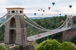 © Licensed to London News Pictures; 14/08/2021; Bristol, UK. Bristol International Balloon Fiesta - Fiesta Fortnight 2021. 50 balloons take off in Bristol this evening from 2 different locations, including from Ashton Court pictured here  flying over the Clifton Suspension Bridge as well as Queens Square as the Bristol Balloon Fiesta continues across the city. This display will be the third mass ascent of the Fiesta Fortnight and is set to be the largest ascent so far. 'Fiesta Fortnight', will take place from Monday 2nd August to Sunday 15th August 2021 and will see hundreds of hot air balloons taking off from multiple locations across the city. The usual Bristol Balloon Fiesta event at Ashton Court is not happening this year because of the covid coronavirus pandemic. Photo credit: Simon Chapman/LNP.