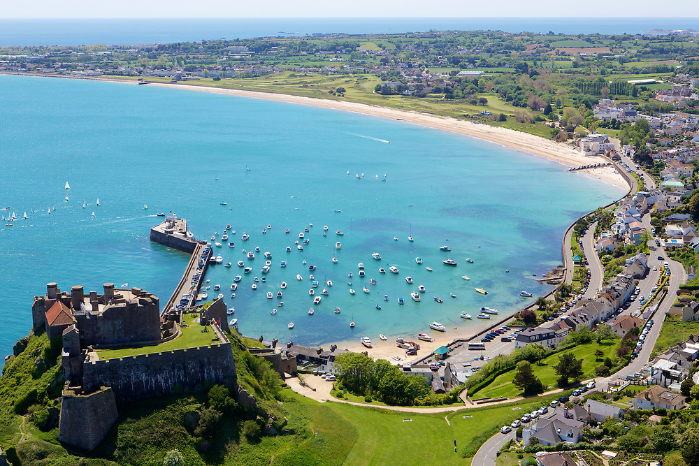 Aerial view of Mont Orgueil Castle, Gorey harbour and pier with the boats moored up and Grouville Bay on a calm, clear sunny day in summer in Jersey, Channel Islands