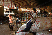 A young boy plays with a plastic gun, leaning on sacks of aluminum cans. Recycling warehouse, big distribution for aluminium cans, and general metals, on the edge of Phnom Penh. Aluminium cans are sold with a street value of about 1$ the kilo, the small warehouse add 10% and all the cans are shipped. already sorted to the big distribution recycling warehouses outside Phnom Penh. Here the aluminium cans are squashed into bricks and stacked or placed in mountains for export to Thailand and Vietnam for truning back into the raw material.