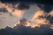 Rays of golden sunset spotlight cumulus clouds over Appenzell village, in Switzerland, Europe.