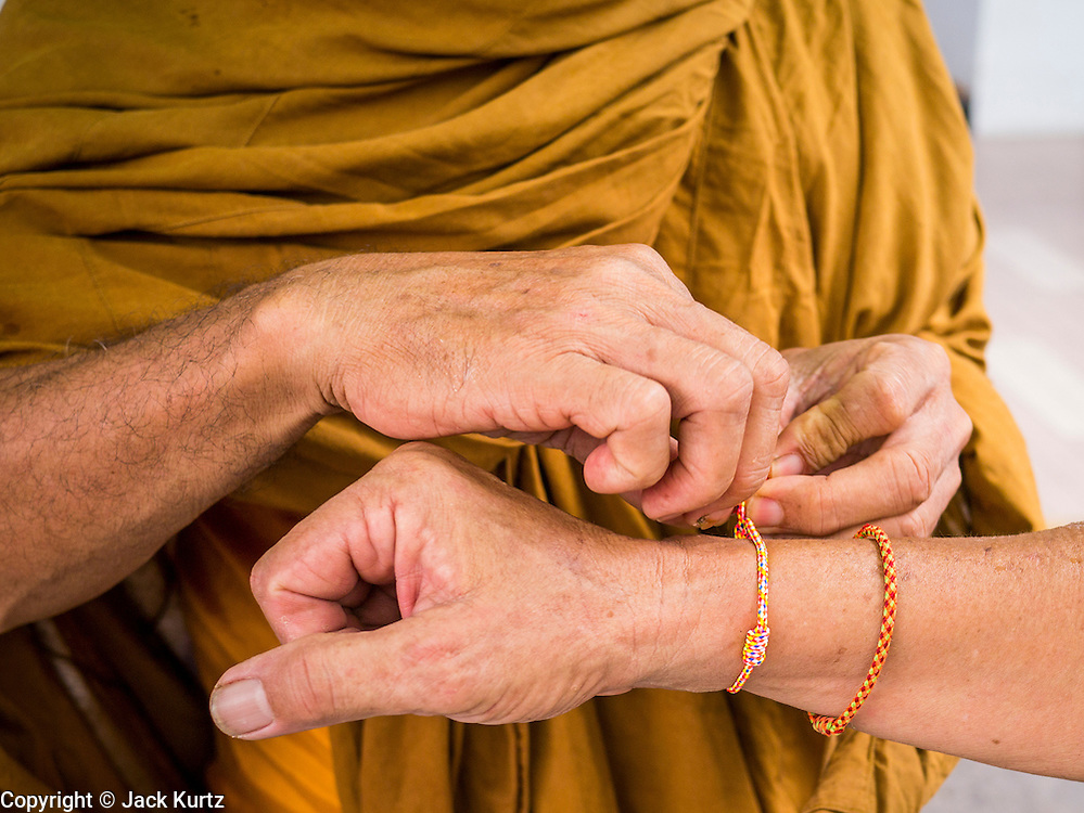 02 NOVEMBER 2012 - HAT YAI, SONGKHLA, THAILAND: A monk ties a string with a Buddhist blessing to a man's wrist in Hat Yai, Songkhla, Thailand. Hat Yai is the commercial center of south Thailand and a popular weekend vacation destination for Malaysian and Singaporean tourists.    PHOTO BY JACK KURTZ
