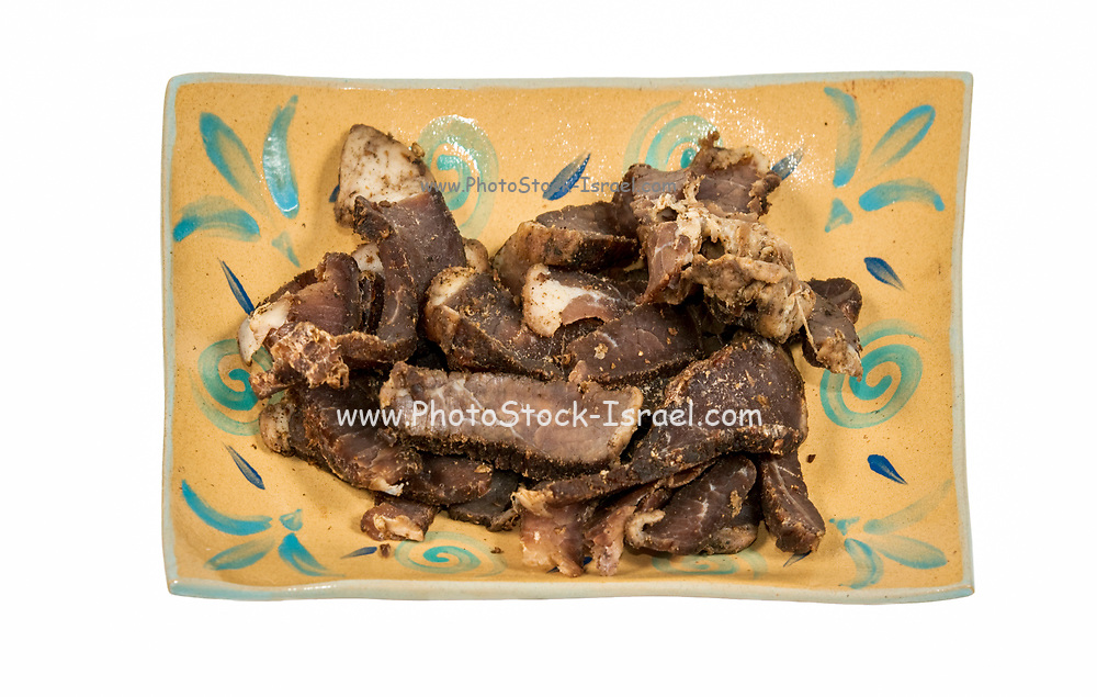 A plate of pieces of Biltong - South African dried meat on white background