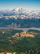 Aerial view of the Redoubt Volcano, shrouded in the clouds, with Tuxedni Bay in the foreground, Lake Clark National Park, Alaska.