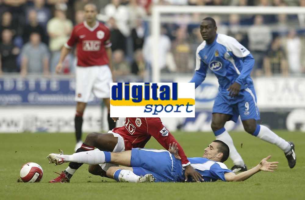 Photo: Aidan Ellis.<br /> Wigan Athletic v Manchester United. The Barclays Premiership. 14/10/2006.<br /> Wigan's Paul Scharner tackles United's louis Saha