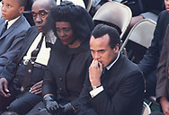 Harry Belafonte, Coretta Scott King and the King family at the interment of Reverend Martin Luther King Jr. at Morehouse College.  I made this photograph from a four by ten foot wood plank that was attached  by four wires (one from each corner) that went up to one wire which was attached to a giant crane that hovered over the internment site.  There was no communication between the owner of the crane and the photographers on this flimsy  contraption.  <br /> Photo by Dennis Brack bb72
