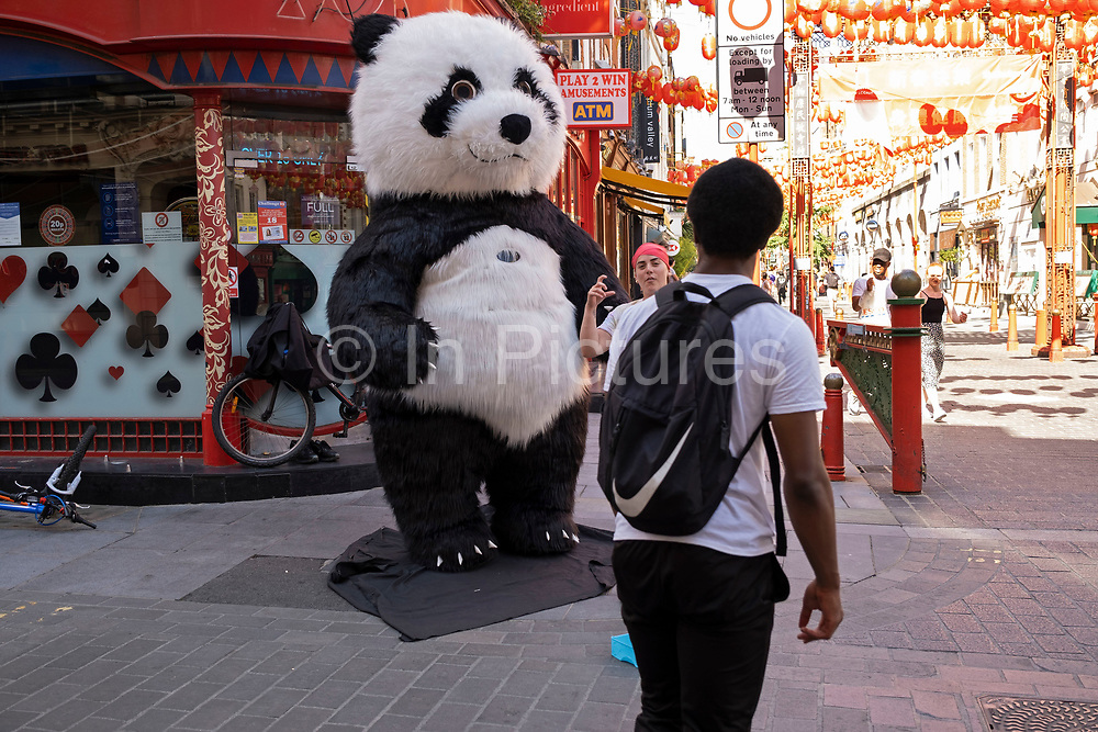 Trying to earn some money from tourists dressed up as a Giant Panda on the corner of Gerrard Street in Chinatown which remains very quiet with a few people visiting Chinese restaurants to pick up food and to see the red lanterns on 26th June 2020 in London, England, United Kingdom. As the July deadline approaces and government will relax its lockdown rules further, the West End remains quiet, while some non-essential shops are allowed to open with individual shops setting up social distancing systems.