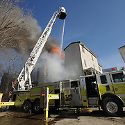 4/8/11 -- BRUNSWICK, Maine. The Brunswick Fire Dept Ladder truck reaches over the top of 18 Oak St on friday afternoon. A fire broke out on friday afternoon there and spread quickly from the entryway on the right side. and consumed nearly the entire apartment building. No one was hurt. Photo by Roger S. Duncan.
