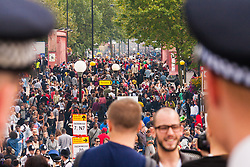 """London, August 24th 2014. Police keep an eye on the teeming Ladbroke Grove as thousands of Londoners of all races and cultures attend Notting Hill Carnival's """"Family friendly"""" day ahead of the main carnival on August Bank Holiday Monday."""