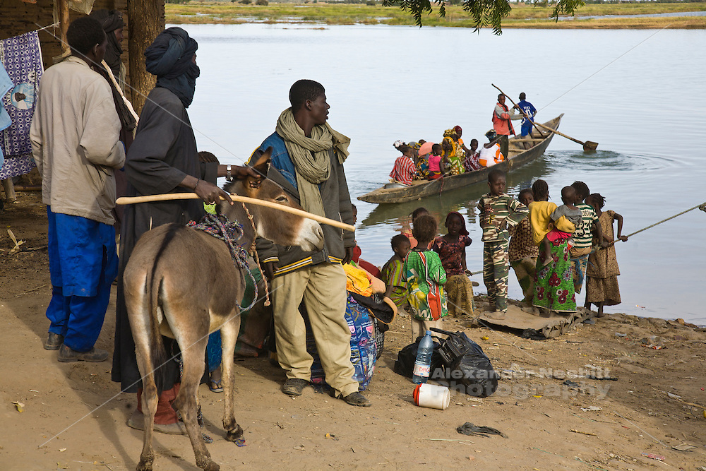 Korioume, Mali 2009 - Boys operating a small rowboat as a ferry are seen transporting a group of women across the Niger River to a neighboring village while the crowd watches the loading and unloading of the commercial ferry nearby.