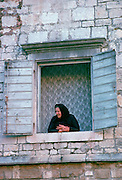 A woman watching from her window in Kotor, Montenegro, - formerly Yugoslavia - a UNESCO World Heritage Site.