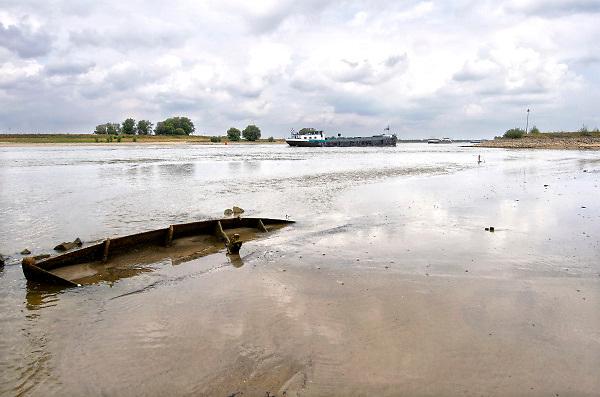 Nederland, Nijmegen, 21-8-2018 Door de aanhoudende droogte staat het water in de rijn, ijssel en waal extreem laag . Schepen moeten minder lading innemen om niet te diep te komen . Hierdoor is het drukker in de smallere vaargeul . Een gezonken houten bootje komt alleen bij dit extreem lage water droog te liggen . Door uitblijven van regenval in het stroomgebied van de rijn komt het record, laagterecord van 6,89 meter uit 2011in zicht . Foto: Flip Franssen