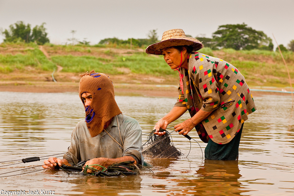 """07 APRIL 2010 - NAKHON PHANOM, THAILAND:  A couple nets fish in a channel in the Mekong River. They said they used to have use a boat for this but now the river is so low they do it on foot. He said he doesn't know why the river is so low, that some people say it's global warming. """"But I don't know what that is. I think it's when the factories send too much smoke into the air, but I don't understand it."""" He went onto to say that they catch much fewer fish now than they did in the past. Normally the river flows completely through the river bed but it's currently running through a channel in the bottom of the river bed. The region is in the midst of a record setting drought and the Mekong River is at its lowest point in nearly 50 years, setting up an environmental disaster the region has never seen before. Many of the people who live along the river farm and fish. They claim their crops yields are greatly reduced and that many days they return from fishing with empty nets. The river is so shallow now that fisherman who used to go out in boats now work from the banks and sandbars on foot or wade into the river. In addition to low river levels the Isan region of Thailand is also in the midst of a record drought and heat wave. Farmers have been encouraged to switch from rice to less water intensive crops and to expect lower yields. Farmers here rely more on rain fall than irrigation to water their crops.       PHOTO BY JACK KURTZ"""