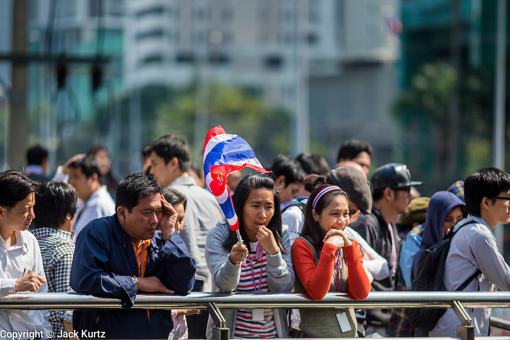 21 JANUARY 2014 - BANGKOK, THAILAND:  Anti-government protestors watch their colleagues march down Thanon Naradhiwas Rajanagarindra during a march by Suthep Thaugsuban. Suthep, the leader of the anti-government protests and the People's Democratic Reform Committee (PDRC), the umbrella organization of the protests, led a march through the financial district of Bangkok Tuesday. Shutdown Bangkok has entered its second week with no resolution in sight. Suthep is still demanding the caretaker government of Prime Minister Yingluck Shinawatra resign and the PM says she won't resign and intends to go ahead with the election.    PHOTO BY JACK KURTZ