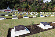 War graves and a cross bearing a sword after a Remembrance Day ceremony at the Yokohama War Cemetery, Hodogaya. Yokohama, Japan. Sunday November 9th 2014