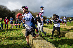 © Licensed to London News Pictures. 05/03/2017. Dorking, UK. Competitors take part in the 2017 Wife Carrying Race in Dorking, Surrey.  The race, which is run over a course of 380m, with both men and women carry a 'wife' over obstacles,  is believed to have originated in the UK over twelve centuries ago when Viking raiders rampaged into the northeast coast of  England carrying off any unwilling local women.  Photo credit: Ben Cawthra/LNP