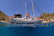Mediterranean Sea off the Turkish coast a man and a woman in their 20s standing on the deck of a yacht as seen from underwater