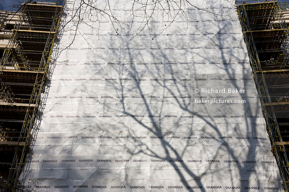 Construction safety sheeting with plain tree shadow at a Skanska building project in Finsbury Circus.