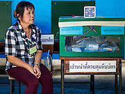 07 AUGUST 2016 - BANGKOK, THAILAND:  An election worker sits next to a ballot box in a polling place in Bangkok. Thais voted Sunday in the referendum to approve a new charter (constitution) for Thailand. The new charter was written by a government appointed panel after the military coup that deposed the elected civilian government in May, 2014. The charter referendum is the first country wide election since the coup.      PHOTO BY JACK KURTZ