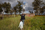 A man and a young boy are walking in the grass around Kakuruk village, Gashish district, in the local government of Barkin Ladi, near Jos, Plateau State, Nigeria. The village, inhabited by Christians from the Berom tribe, has received various attacks by neighbouring Muslim Fulani - a nomadic cattle-herder tribe non-indigenous to Plateau - with the last one on 7th July, 2012, when more than 30 houses were demolished and 8 Christian villagers killed.