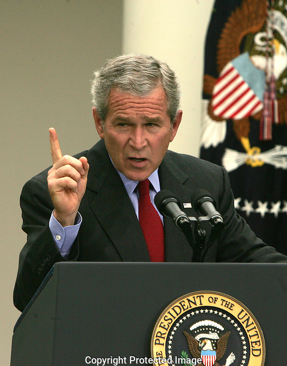 President George W. Bush answers a reporter's question at a press conference in the Rose Garden of the White House on June 14, 2006. Photograph by Dennis Brack
