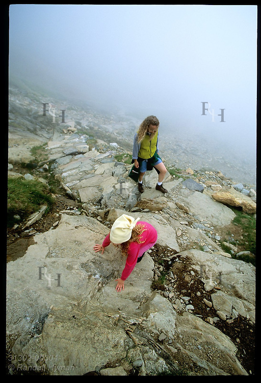 Mother and daughter hike through clouds on Miner's Track up Mount Snowdon (3560') on August morn; Snowdonia National Park, Wales