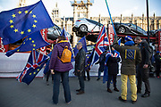 Anti Brexit pro Europe demonstrators protest waving European Union and Union Jack flags as a car transporter passes in Westminster opposite Parliament one week before MPs vote on the finalised deal on 8th January 2019 in London, England, United Kingdom. MPs will vote on Theresa Mays Brexit deal on Tuesday, 15 January, government sources confirmed.