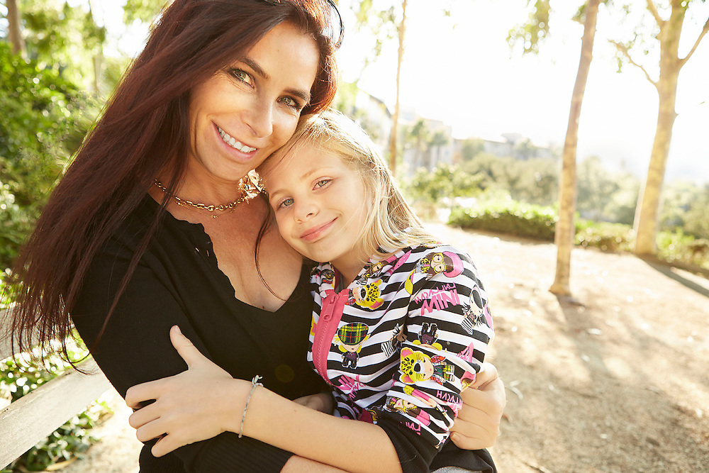 Lifestyle image of mother hugging daughter in her arms