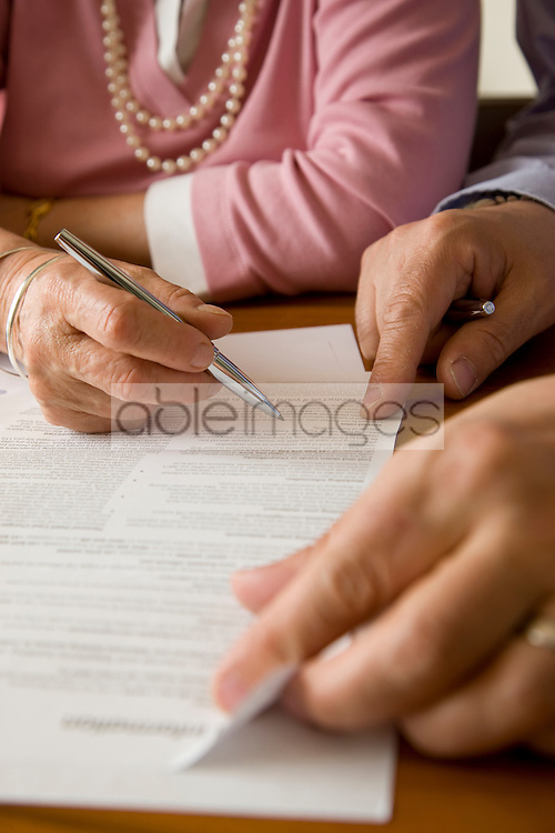 Close up of man and woman hands signing documents