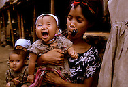 Thailand.  Refugee camp for Karen tribal people who have escaped a brutal regime in Burma/Myanmar.   Keran mother and happy, healthy child