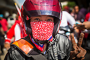 08 MAY 2013 - BANGKOK, THAILAND:   A Red Shirt on a motorcycle in a Red Shirt motorcade to the Thai Parliament. A splinter group of the Red Shirts, Thai supporters of exiled Prime Minister Thaksin Shinawatra, have besieged the Thai Constitutional Court for the last three weeks calling for the resignation of the justices, who have indicated they might oppose a proposed constitutional reform which would grant amnesty to people convicted of political crimes since 2007. This would probably include Thaksin. The justices have refused to step down. Wednesday the protesters moved their protest to the Thai Parliament, which is largely powerless to intervene. PHOTO BY JACK KURTZ