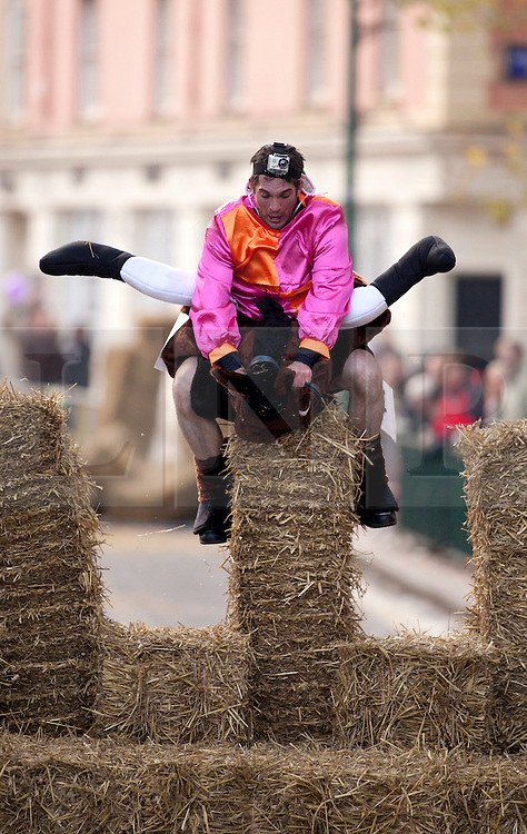 """© under licence to London News Pictures 28/11/2010 today picture. Birmingham`s wackiest Christmas event, the annual Pantominme Horse Grand National. The event that sees riders and horses race up and down Broad Street in the City Centre jumping over and even Through straw bales. Picture shows a sequence of rider Joel Hicks on his steed """"Viagra"""" as he falls at a fence and completes the corse last..Picture credit: Dave Warren/London News Pictures..."""