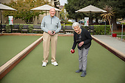 A senior women rolling a bocce ball with friend