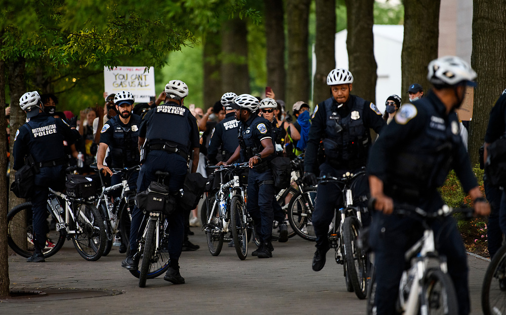 Black Lives Matter protesters confront the police shadowing them as they march towards the capitol. Some felt they were threating the group.