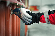An expeditionary shakes hands with a frozen glove hanging on Module 7 under construction at the Pedro Vicente Maldonado Antarctic Station in Shetland peninsula.