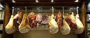Shop window display of cured meats, hams, pork shoulders, at Dalmayr food shop and delicatessen in Munich, Bavaria, Germany