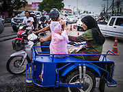 08 JULY 2013 - PATTANI, PATTANI, THAILAND:   A Muslim family leaves a grocery store in Pattani after stocking up before Ramadan Monday afternoon. Ramadan starts July 9 and Monday was the last day observant Muslims were able to eat and drink during daylight hours. Muslims fast during the holy month of Ramadan, taking breakfast before dawn and not eating again until after sunset. The restaurants in Pattani, a Muslim majority city in southern Thailand, were packed Monday afternoon and evening.  PHOTO BY JACK KURTZ