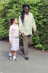 Single father walking along path talking and holding hands with young daughter,