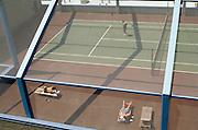 people sunbathing on a rooftop tennis court
