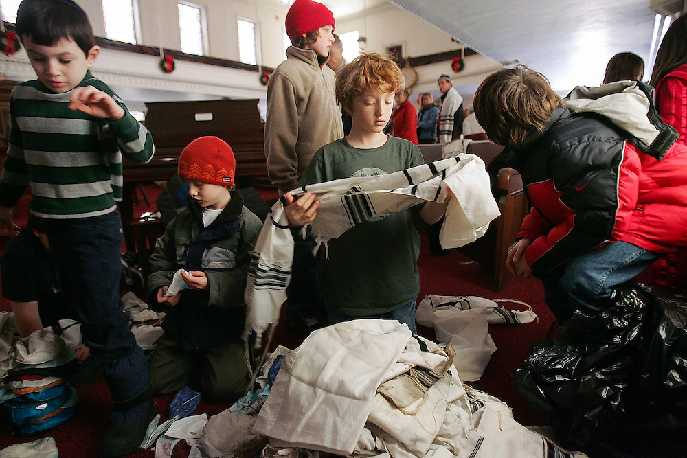 (121507 Glouchester, MA)   Children of the Temple Ahavat Achim go through salvaged prayer shawls and fold the ones that can be saved.  After their temple burnt down early Saturday morning, the congregation held their service at the Unitarian Universalist Church a few doors down.  A multi-alarm blaze on Middle St. took one life and destroyed a synagogue in Glouchester.