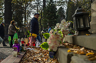 People walk into the Rakowicki cemetery in Krakow with plastic bags filled with flowers, Poland 2019.