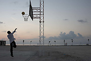 A solo teenage player takes a shot at the net on a basketball court at the Cyprea Marine Foods (CMF) processing factory on Himmafushi Island, Maldives in the Indian Ocean. It is dusk near the equator and soon dark. The landscape is barren except for some young trees on the waterfront where two people are walking in the cool tropical air. Seen in the last, darkening light of day, the player leaps upwards and his arm stays where his ball left his hand to roll around the ring. The man is enjoying some leisure time at the end of his working day, possibly an employee of CMF who handle newly-caught tuna fish for export to the EU and the UK's supermarket food industry.