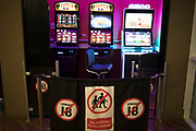 Over 18s only gambling barrier blocking off the area where slot machines, also known as fruit machines or gaming machines stand in a service station near London, England, United Kingdom. Betting is seen as an activity that requires strict controls so that under 18 year olds do not play them, and that children are not allowed or encouraged into the area where gambling takes place.
