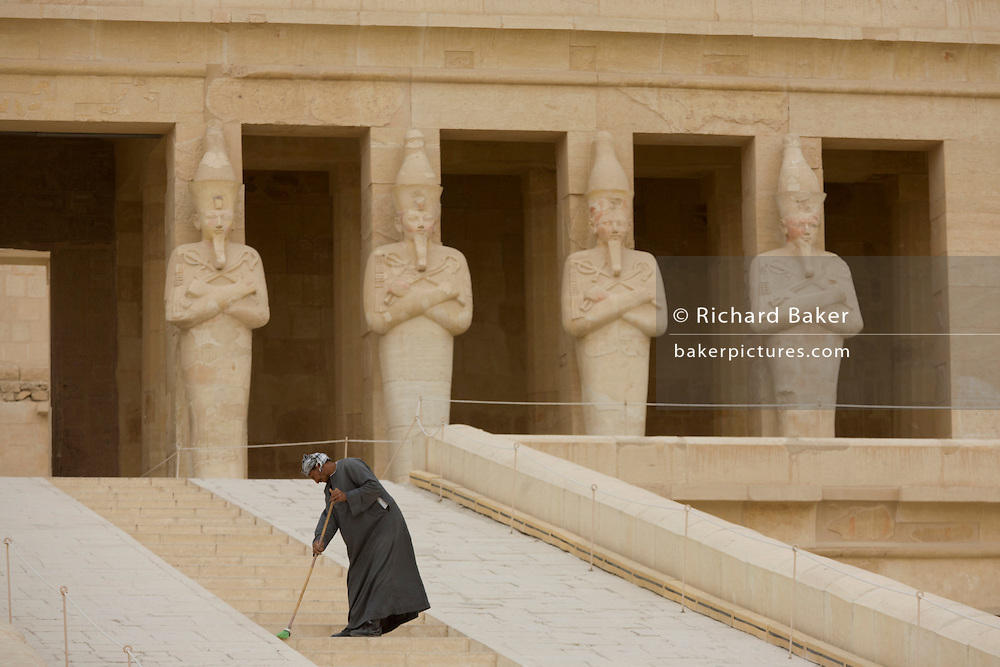 """A caretaker sweeps dusty steps at the ancient Egyptian Temple of Hatshepsut near the Valley of the Kings, Luxor, Nile Valley, Egypt. The Mortuary Temple of Queen Hatshepsut, the Djeser-Djeseru, is located beneath cliffs at Deir el Bahari (""""the Northern Monastery""""). The mortuary temple is dedicated to the sun god Amon-Ra and is considered one of the """"incomparable monuments of ancient Egypt."""" The temple was the site of the massacre of 62 people, mostly tourists, by Islamists on 17 November 1997."""