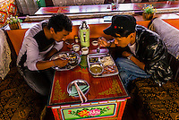 Local Tibetan men eating lunch at Tashi Restaurant, Tsedang, Tibet (Xizang), China.