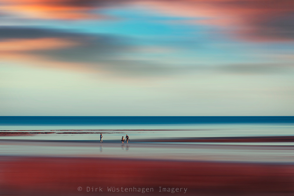 Abstract beach scene with walkers in evening light