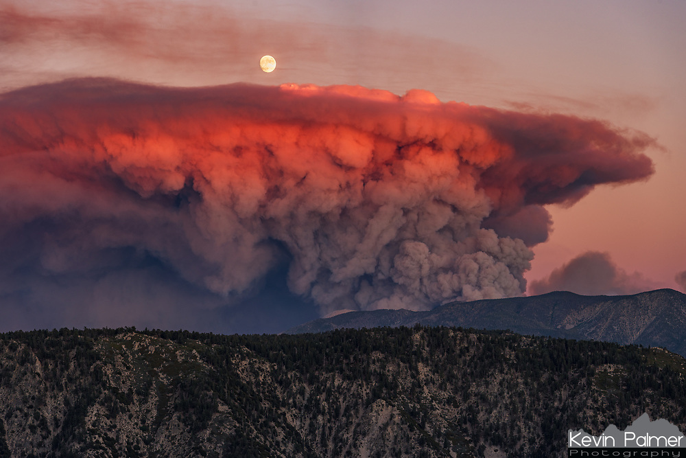 Fueled by hot, dry weather and gusty winds, it only took a day and a half for the Apple Fire to explode to 32 square miles. As the forest went up in flames, the plume of smoke ballooned to 25,000 feet. That's more than twice the height of San Gorgonio Mountain, Southern California's highest peak seen in the middle of this photo. The behavior of this fire is extreme enough to make it's own weather. Pyrocumulus is a type of cloud formed when intense heat creates an updraft similar to a thunderstorm. Pyrocumulus lofts embers high into the air, creates strong unpredictable outflow winds at the surface, and in rare cases even generates lightning. The same phenomena is seen in volcanic eruptions. All of this hampers firefighting efforts and causes the flames to expand even more. But even in the devastation, there was beauty. From my vantage point northwest of the blaze, the smoke plume took on a deep red glow at sunset before the 97% full moon rose above it.