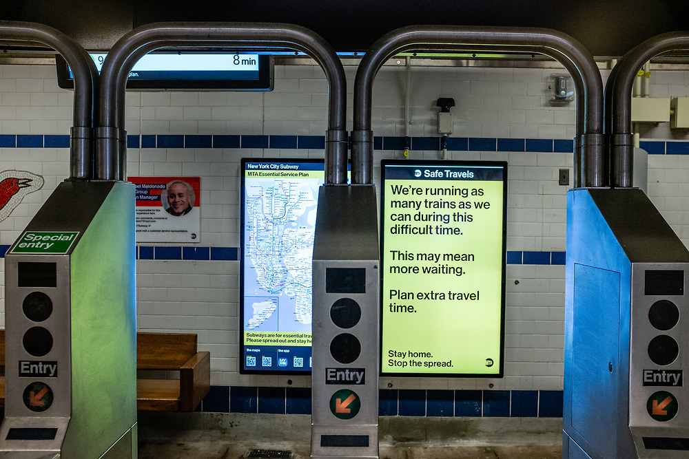 Brooklyn, NY. 5 April 2020. Signs in the entrance to the Avenue J station on the subway's Q line announce service restrictions, and ask that all non-essential riders stay home. This sign announces reduced service and asks riders to expect additional travel time.